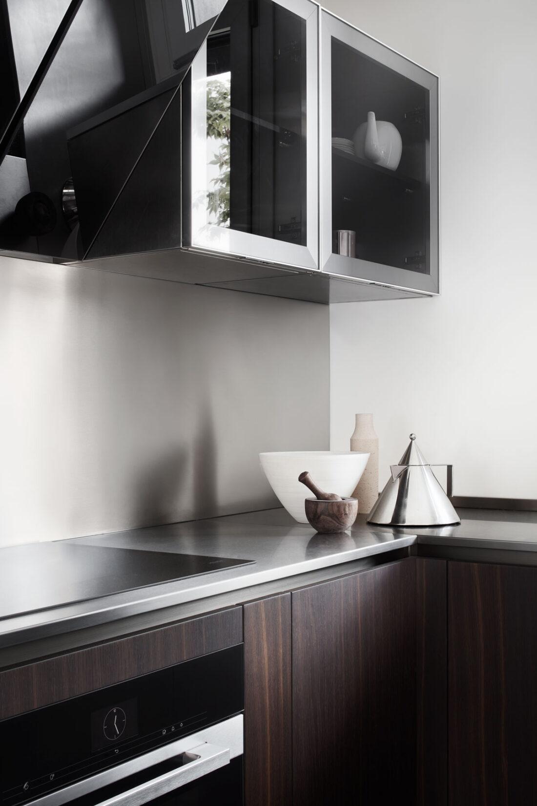 Cucina moderna in acciaio e legno con vasi raffinati ed elettrodomestici di lusso
