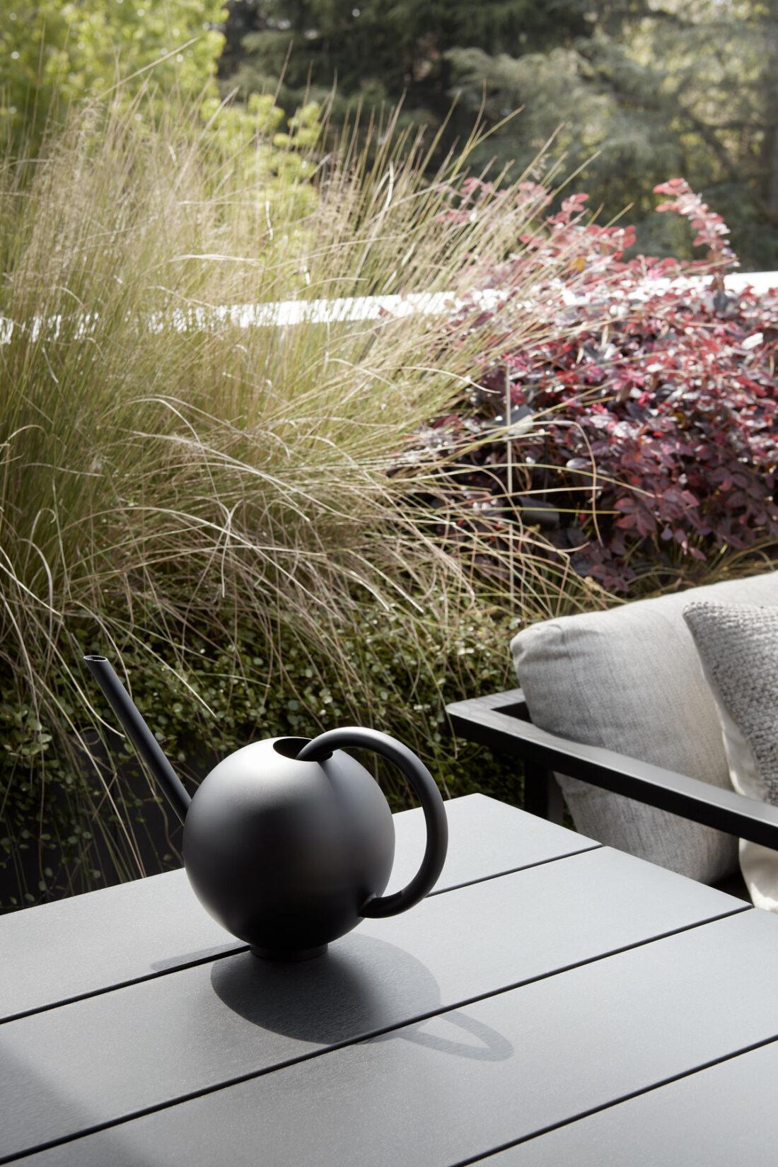 annaffiatoio nero moderno su un tavolo di una terrazza di un attico