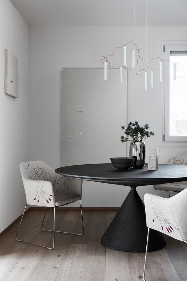 Tavolo moderno con sedie in tessuto, lampada a sospensione artistica e due quadri