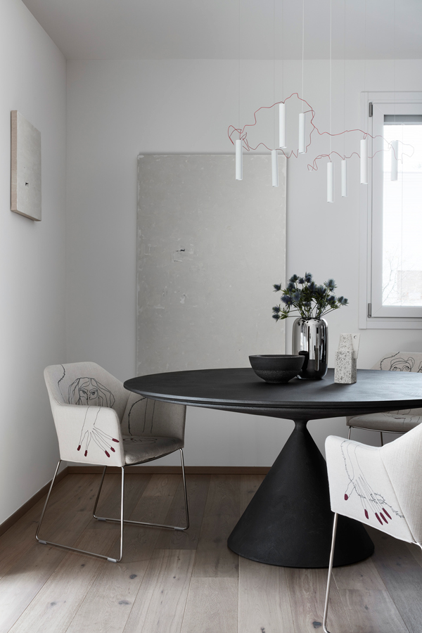 modern table with fabric chairs, artistic suspension lamp and two paintings
