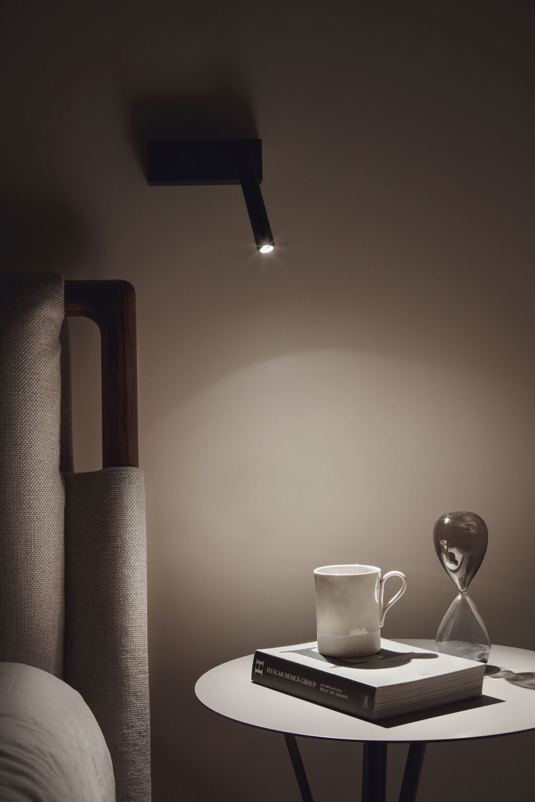 bedside table with accessories and a reading lamp