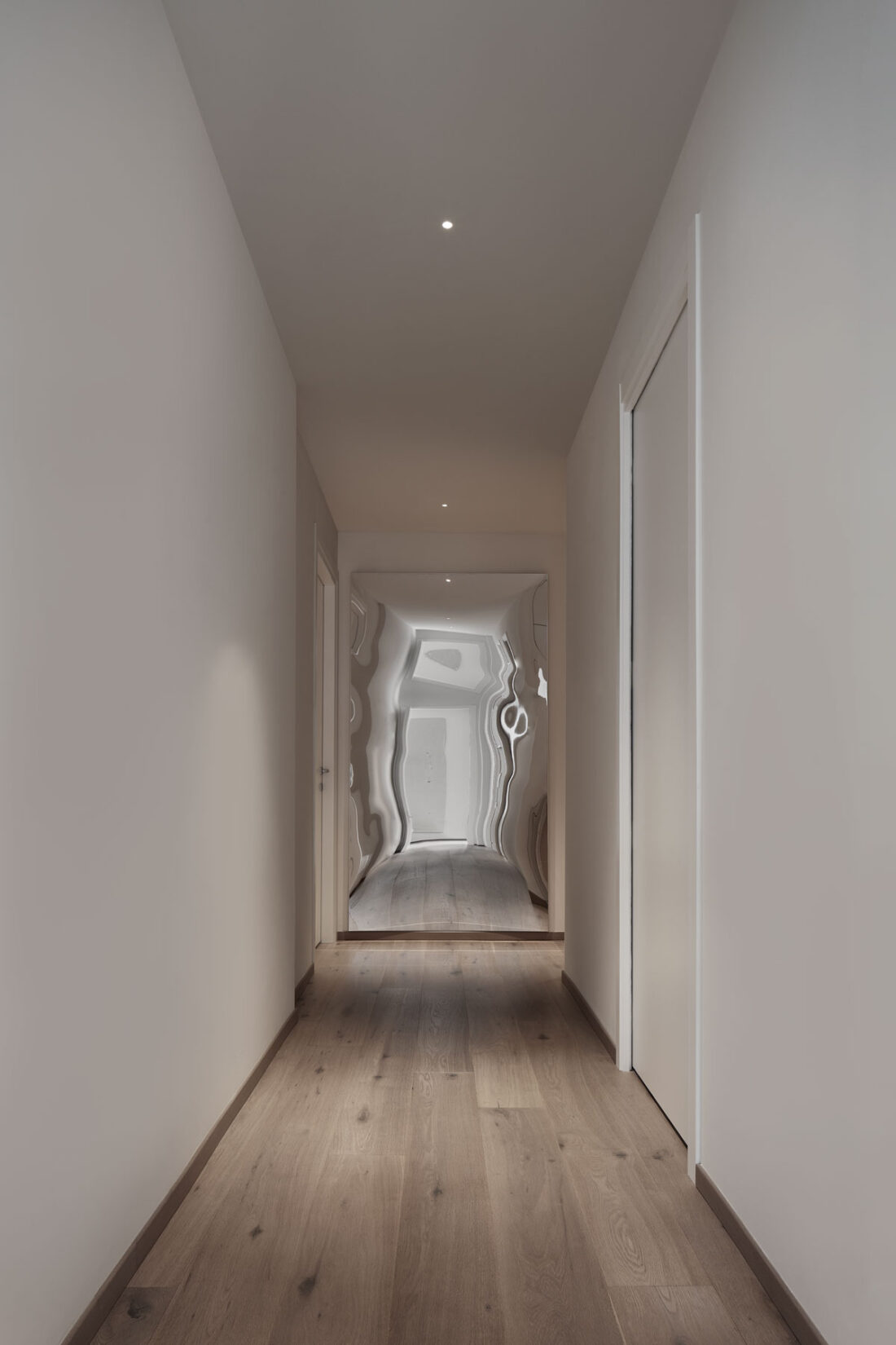 minimal white corridor with an artistic distorting mirror at night