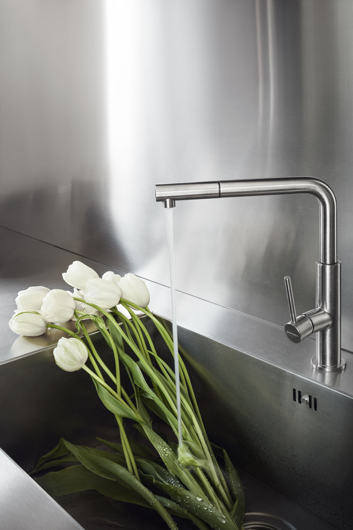 white tulips in a modern stainless steel kitchen sink