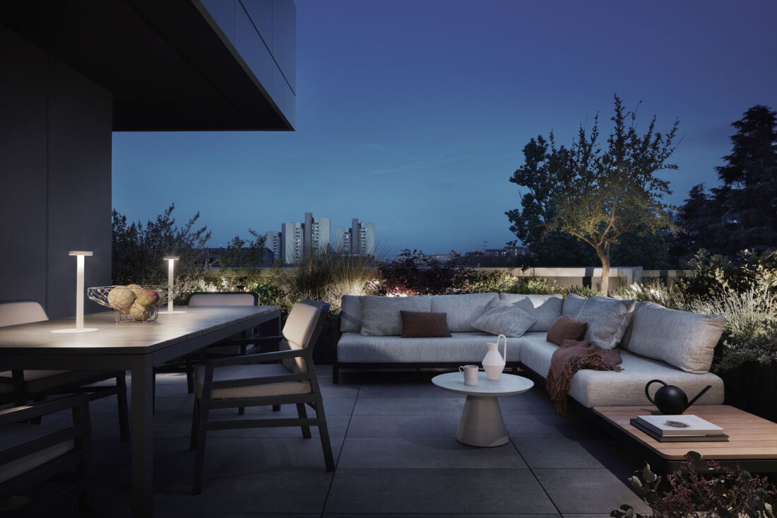 modern penthouse terrace with outdoor furniture and plants during night