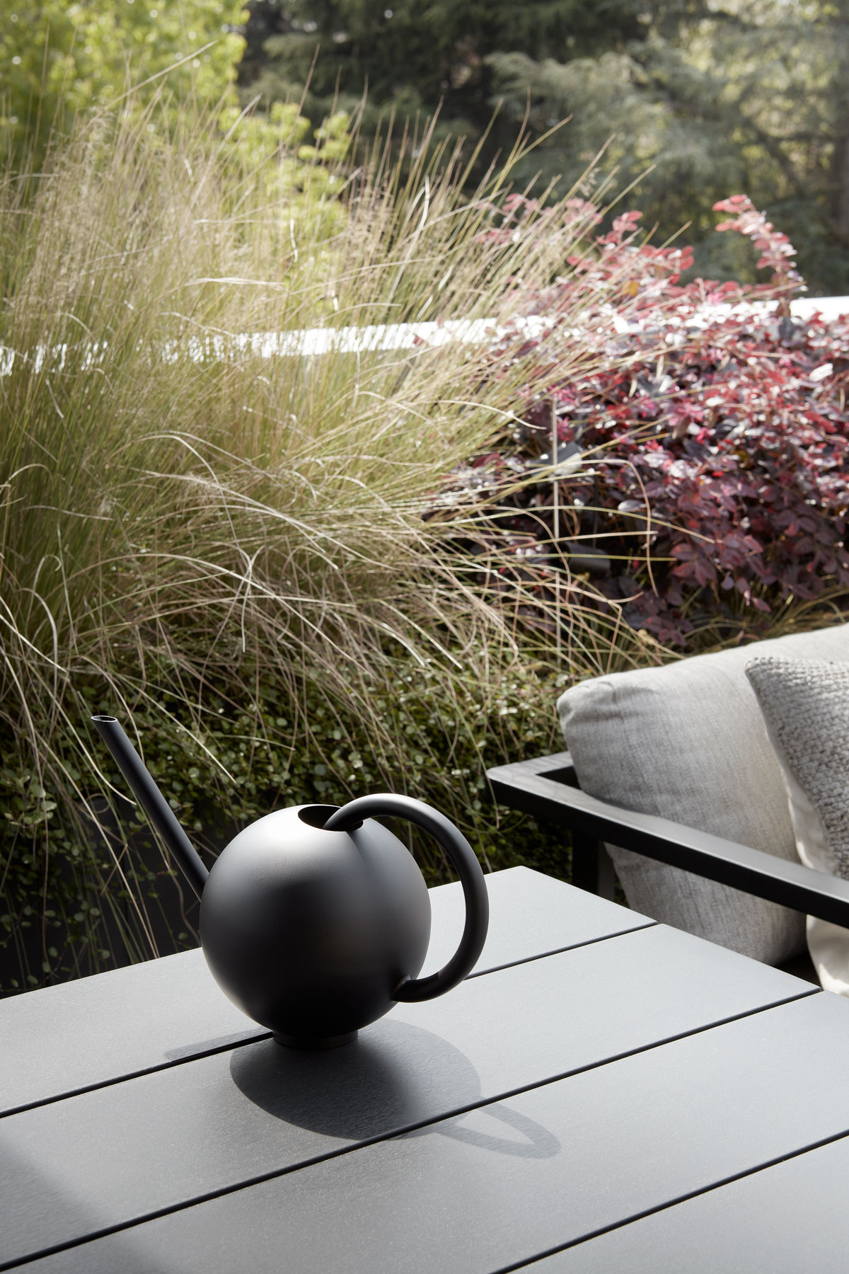 modern black watering can on a table in a penthouse terrace